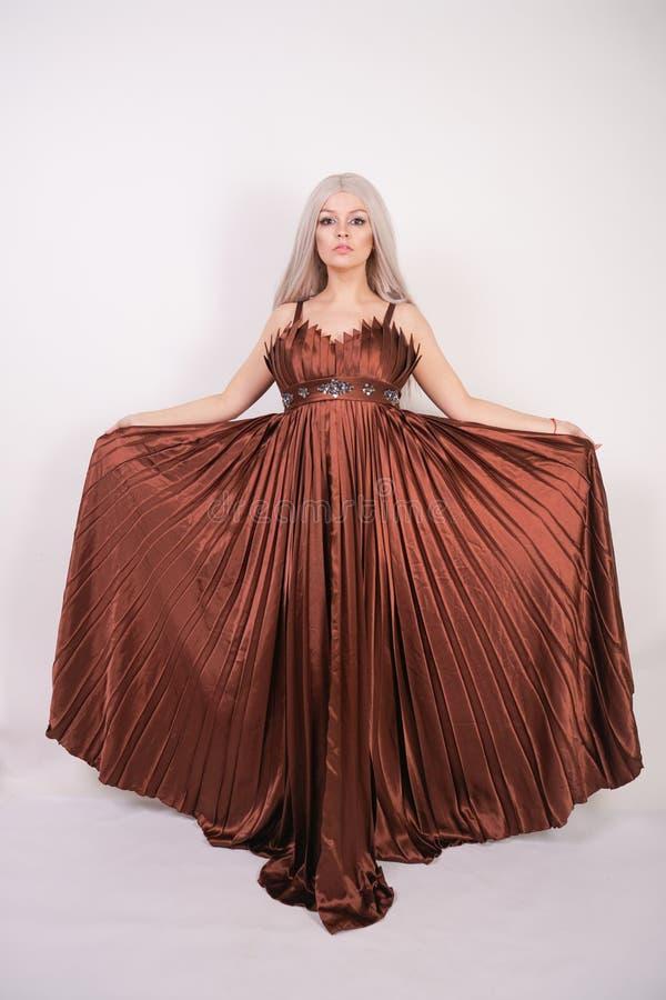 Το ξανθό καυκάσιο πρότυπο κορίτσι πολυτέλειας στο μακρύ φόρεμα βραδιού χρώματος σοκολάτας φιαγμένο από πτυχωμένο ύφασμα που κυματ στοκ εικόνα με δικαίωμα ελεύθερης χρήσης