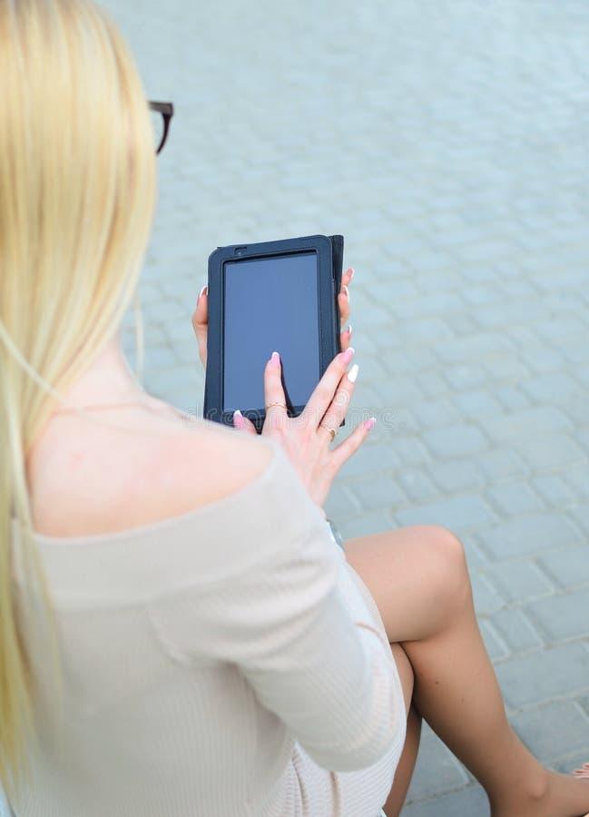 Το ξανθό κορίτσι απολαμβάνει ένα smartphone κατά τη διάρκεια της ημέρας υπαίθρια Επικοινωνία στα κοινωνικά δίκτυα σερφ Διαδικτύου στοκ εικόνα με δικαίωμα ελεύθερης χρήσης