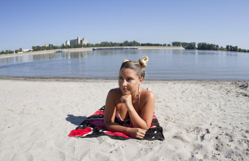 Το ξανθό κορίτσι θέτει στην άμμο σε ένα μαγιό μπικινιών Η παραλία είναι Oficirac Novi Sad στοκ εικόνες