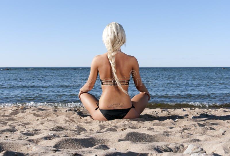 το ξανθό κορίτσι παραλιών meditat στοκ εικόνα με δικαίωμα ελεύθερης χρήσης