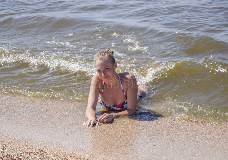 Το ξανθό κορίτσι σε ένα μπικίνι που βρίσκεται στην παραλία και τα κύματα καταβρέχουν σε το Όμορφη νέα γυναίκα σε ένα ζωηρόχρωμο μ στοκ φωτογραφία