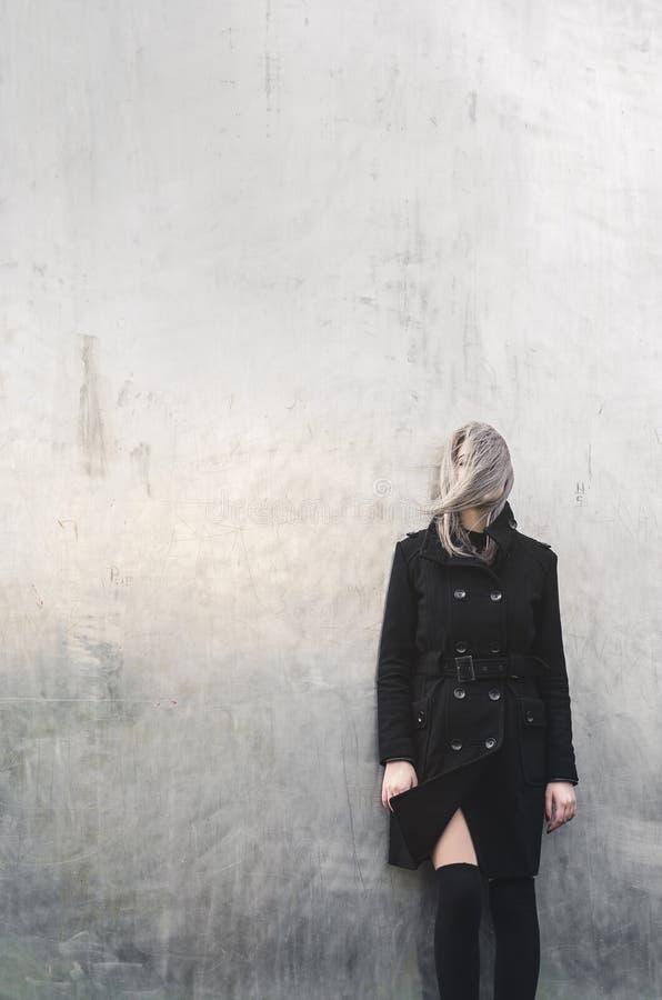 Το ξανθό κορίτσι σε προκλητικό θέτει με το καλυμμένο πρόσωπο στοκ φωτογραφία