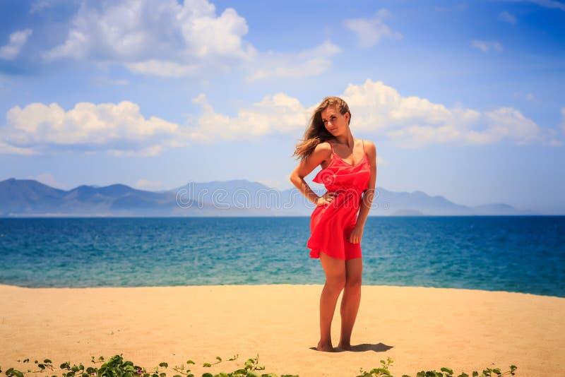 το ξανθό κορίτσι στις κόκκινες στάσεις στην άμμο κρατά το χέρι στο ισχίο το μεσημέρι στοκ εικόνες