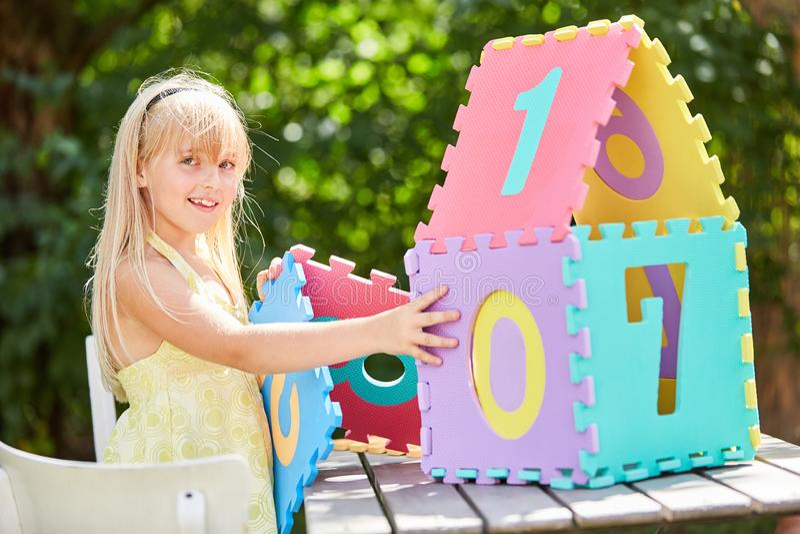 Το ξανθό κορίτσι χτίζει ένα μικροσκοπικό σπίτι στοκ εικόνα