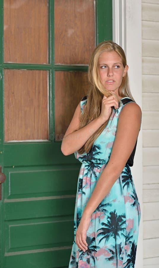 Το ξανθό πρότυπο μόδας θέτει κοντά στο κλείνω με παντζούρια σπίτι στοκ εικόνα