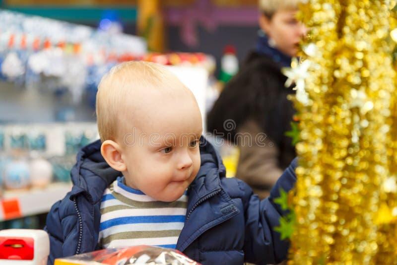 Το ξανθό babe κάθεται σε ένα κάρρο υπεραγορών και επιλέγει ένα χριστουγεννιάτικο δέντρο στο κατάστημα στοκ εικόνα με δικαίωμα ελεύθερης χρήσης