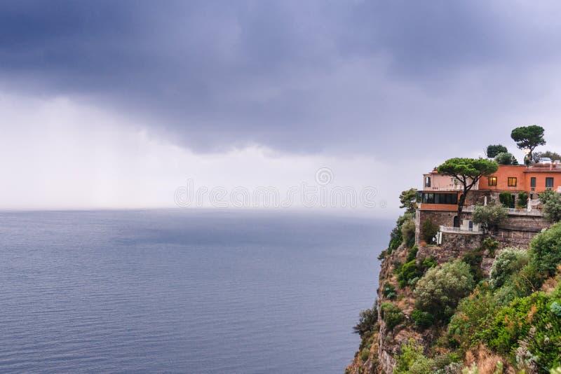 Το ξενοδοχείο στην άκρη του βουνού, εν όψει της βροχής θάλασσας καλύπτει πέρα από όμορφο Σορέντο, κόλπος Meta στην Ιταλία, ταξίδι στοκ φωτογραφία