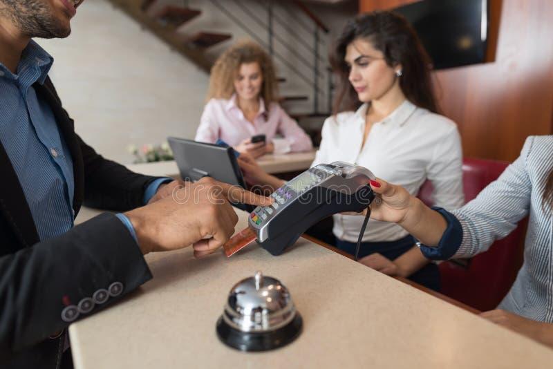 Το ξενοδοχείο επιχειρησιακών ανδρών πληρώνει για το δωμάτιο με την εγγραφή ρεσεψιονίστ γυναικών πιστωτικών καρτών στην υποδοχή στοκ φωτογραφίες με δικαίωμα ελεύθερης χρήσης