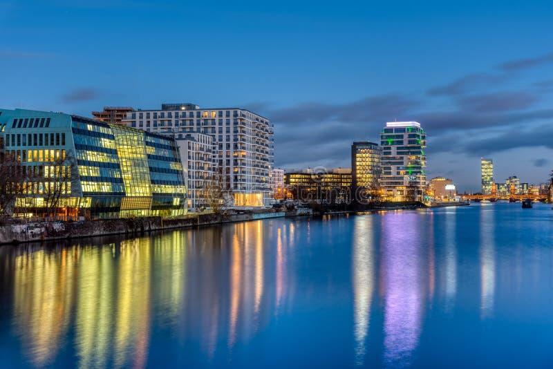 Το ξεφάντωμα ποταμών στο Βερολίνο τη νύχτα με τα σύγχρονα κτήρια στοκ εικόνα