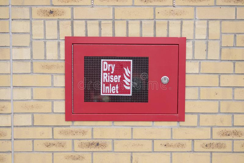Το ξηρό κόκκινο κιβωτίων κολπίσκων μετωπών στο τουβλότοιχο για τις υπηρεσίες πυρόσβεσης έκτακτης ανάγκης ποτίζει τη σύνδεση για τ στοκ φωτογραφία