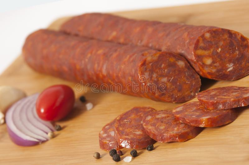 Το ξηρό λουκάνικο χοιρινού κρέατος τεμαχίζει ελαφρώς την άσπρη καρυδιά που καπνίζεται στοκ φωτογραφίες
