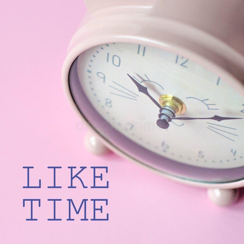 Το ξυπνητήρι σε ένα ρόδινο υπόβαθρο και το κείμενο όπως το χρόνο στοκ εικόνα