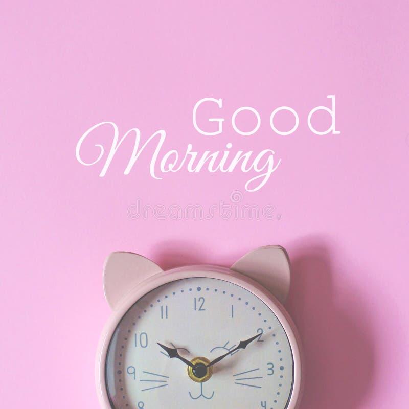 Το ξυπνητήρι σε ένα ρόδινο υπόβαθρο και τη καλημέρα κειμένων στοκ εικόνα με δικαίωμα ελεύθερης χρήσης