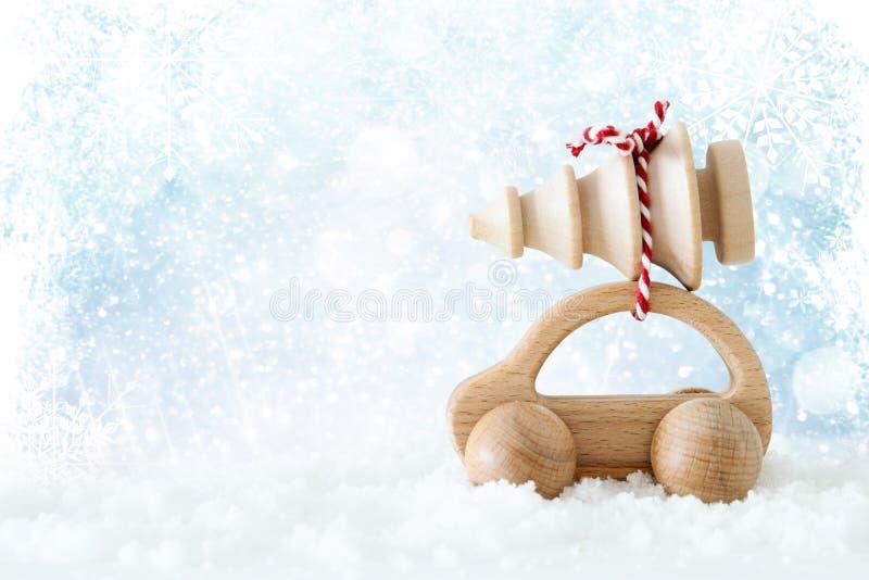 Το ξύλινο αυτοκίνητο που φέρνει ένα χριστουγεννιάτικο δέντρο μπροστά από ακτινοβολεί υπόβαθρο στοκ εικόνες