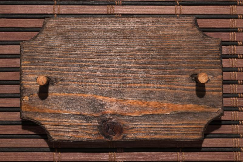 Το ξύλινο διαμορφωμένο πλαίσιο φιαγμένο από ξύλο με ένα ξύλινο φίμωμα είναι σε ένα χαλί μπαμπού στοκ εικόνες