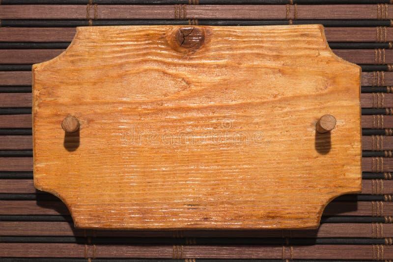 Το ξύλινο διαμορφωμένο πλαίσιο φιαγμένο από ξύλο με ένα ξύλινο φίμωμα είναι σε ένα χαλί μπαμπού στοκ φωτογραφία με δικαίωμα ελεύθερης χρήσης