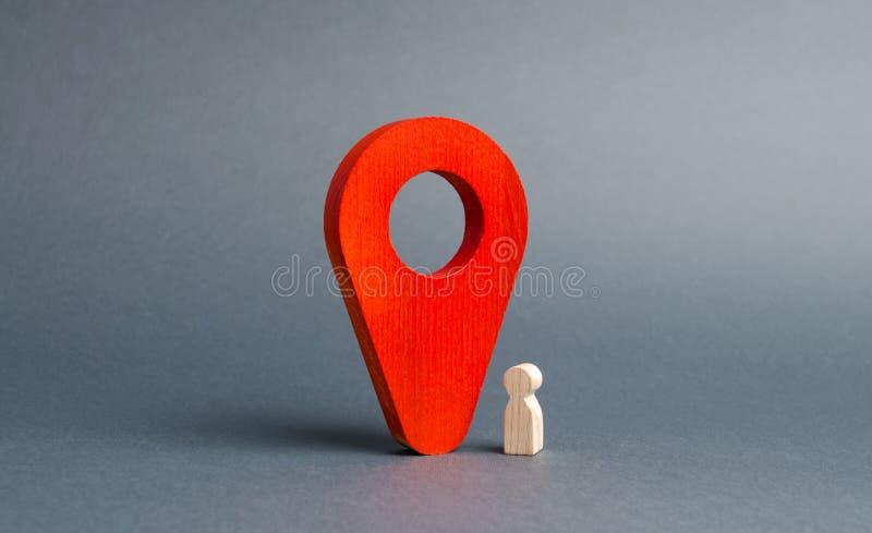 Το ξύλινο ειδώλιο του παιδιού στέκεται κοντά σε έναν τεράστιο κόκκινο δείκτη ακολουθώντας τη θέση του παιδιού σε πραγματικό - χρό στοκ εικόνα με δικαίωμα ελεύθερης χρήσης