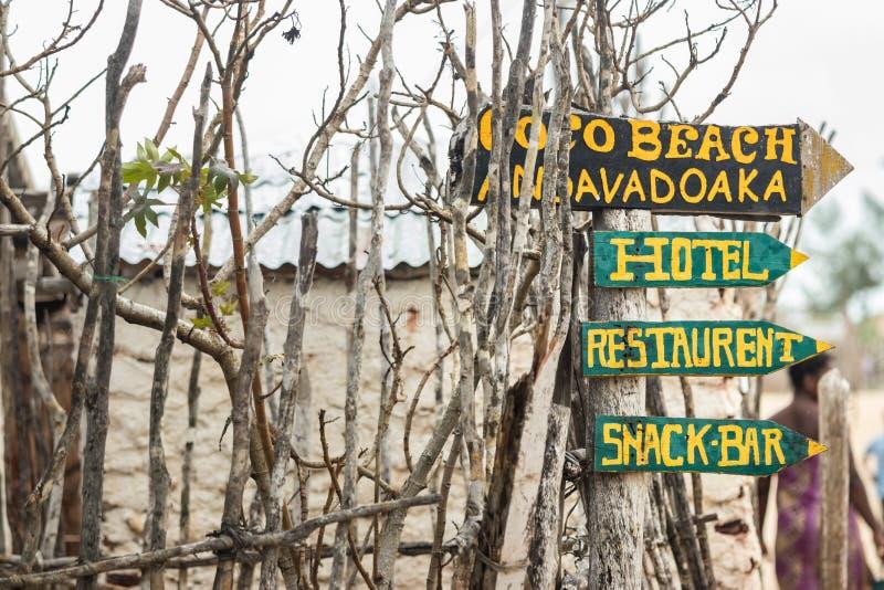 Το ξύλινο σημάδι επιβιβάζεται στην ένδειξη των κατευθύνσεων στα ξενοδοχεία και τους φραγμούς σε Andavadoaka, Μαδαγασκάρη στοκ φωτογραφία