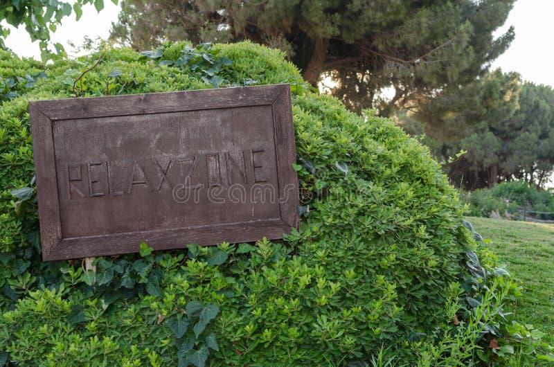 Το ξύλινο σημάδι χαλαρώνει τη ζώνη στο μεγάλο πράσινο θάμνο στο πάρκο στοκ φωτογραφίες με δικαίωμα ελεύθερης χρήσης