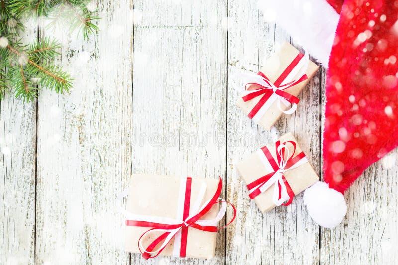 Το ξύλινο υπόβαθρο διακοπών Χριστουγέννων με το έλατο διακλαδίζεται, καπέλο Santa και κιβώτια δώρων που διακοσμούνται με το χιόνι στοκ φωτογραφίες