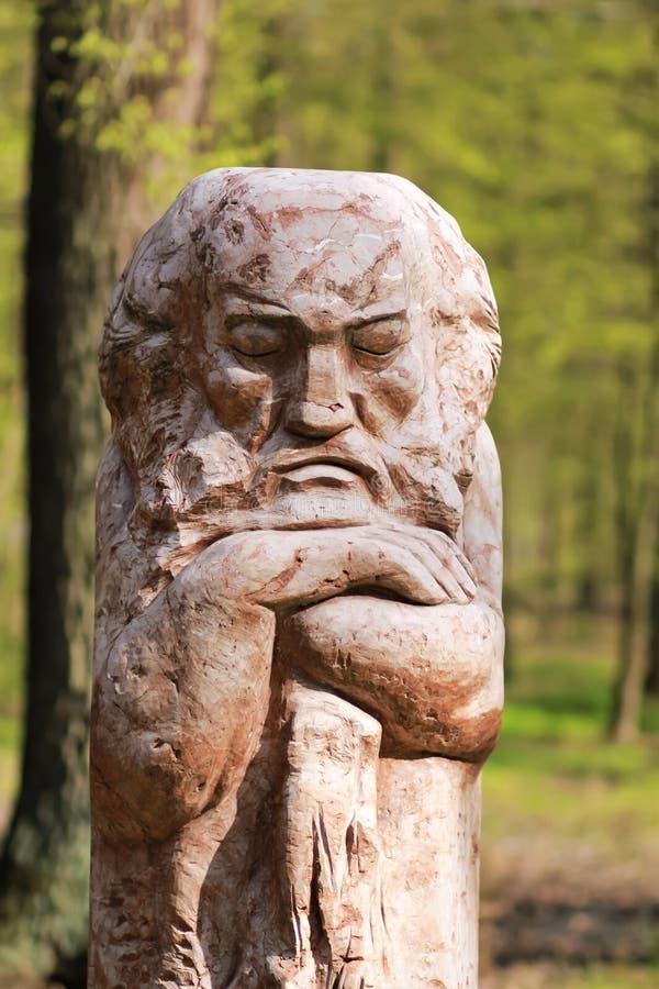 Το ξύλινο χαρασμένο άγαλμα ενός μυθικού χαρακτήρα παραμυθιού, διακόσμηση τοπίων πάρκων ενάντια στην πρασινάδα θόλωσε το υπόβαθρο στοκ εικόνες