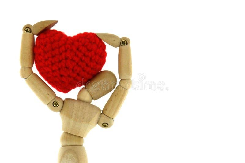 Το ξύλινο μανεκέν φέρνει την καρδιά πλέκει με το νήμα στον ώμο στοκ φωτογραφία