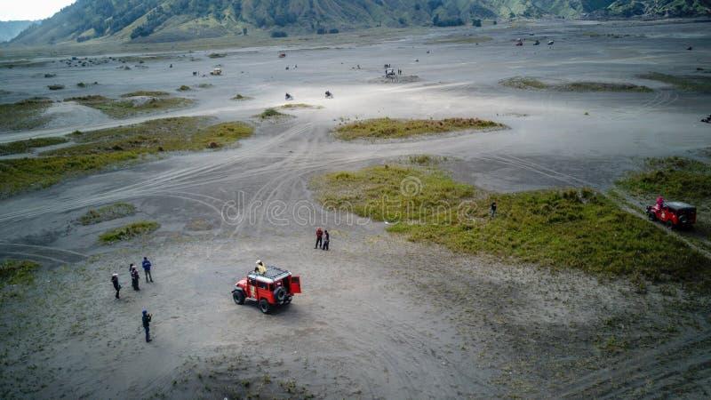 Το οδηγώντας τζιπ περιπέτειας 4WD στο όμορφο ενεργό ηφαίστειο με τον καπνό τοποθετεί Bromo στοκ εικόνα