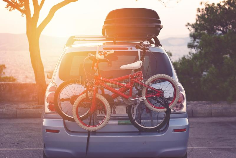 Το οικογενειακό αυτοκίνητο με τα μικρά ποδήλατα παιδιών βασανίζει, έτοιμος για το ταξίδι, που κάνει ένα σπάσιμο στο χώρο στάθμευσ στοκ εικόνα