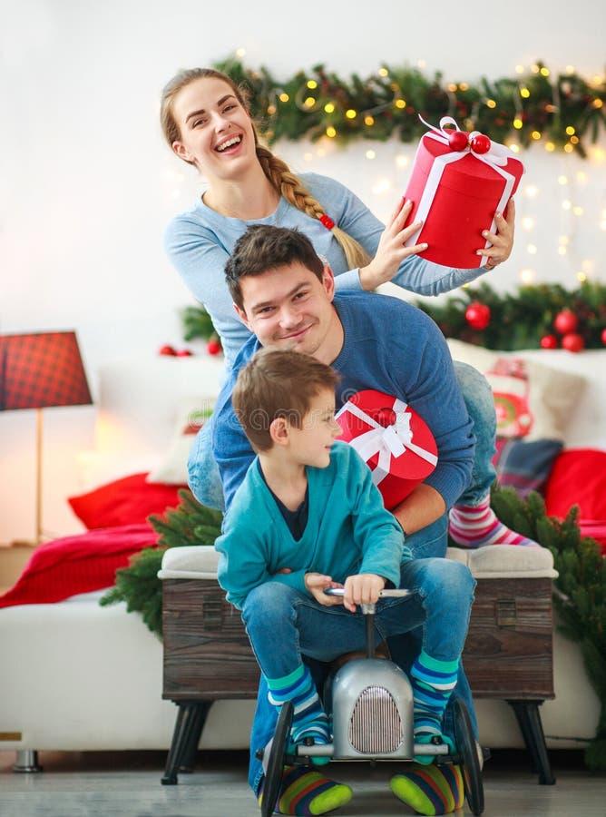 Το οικογενειακό ζεύγος με ένα αγόρι με τα δώρα έχει το παιχνίδι διασκέδασης στο σπίτι στις διακοσμήσεις Χριστουγέννων στοκ εικόνα με δικαίωμα ελεύθερης χρήσης