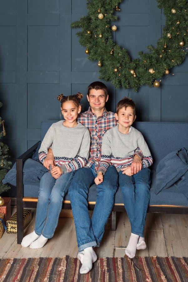 Το οικογενειακό πορτρέτο, μπαμπάς με δύο παιδιά κάθεται στον καναπέ χαμογελώντας στο διακοσμημένο δωμάτιο του νέου έτους στοκ εικόνες