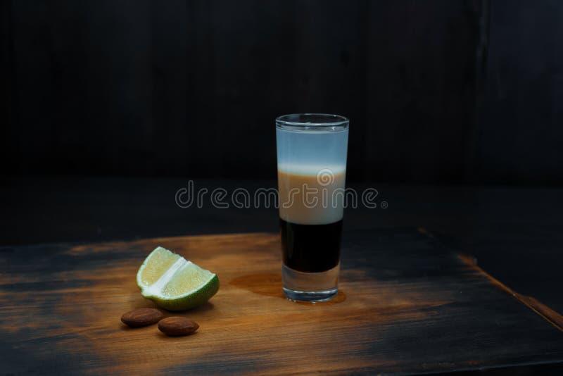 Το οινοπνευματώδες κοκτέιλ διπλός-στρώματος με το σιρόπι σοκολάτας και το σιρόπι καρύδων στέκεται σε έναν εκλεκτής ποιότητας ξύλι στοκ φωτογραφία με δικαίωμα ελεύθερης χρήσης