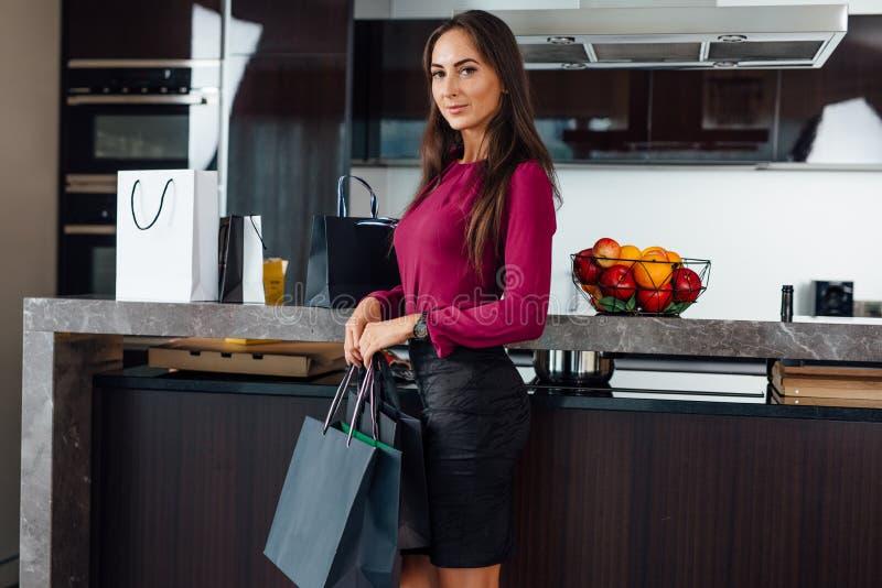 Το ολόκληρο πορτρέτο της νέας μοντέρνης γυναίκας με τις αγορές τοποθετεί τη στάση στην κουζίνα σε σάκκο στοκ φωτογραφία