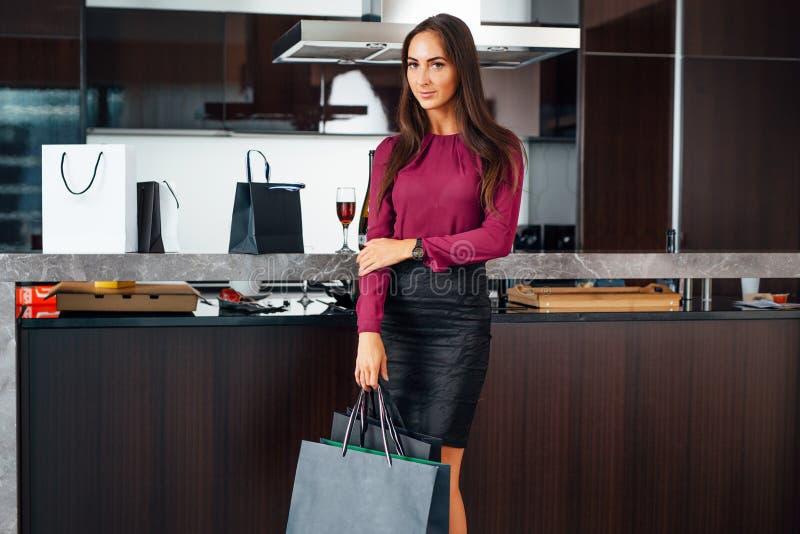 Το ολόκληρο πορτρέτο της νέας μοντέρνης γυναίκας με τις αγορές τοποθετεί τη στάση στην κουζίνα σε σάκκο στοκ φωτογραφίες