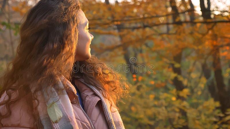 Το οπίσθιο πορτρέτο του όμορφου σγουρός-μαλλιαρού καυκάσιου κοριτσιού την γύρισε πίσω επάνω στη κάμερα στο φθινοπωρινό πάρκο στοκ εικόνες