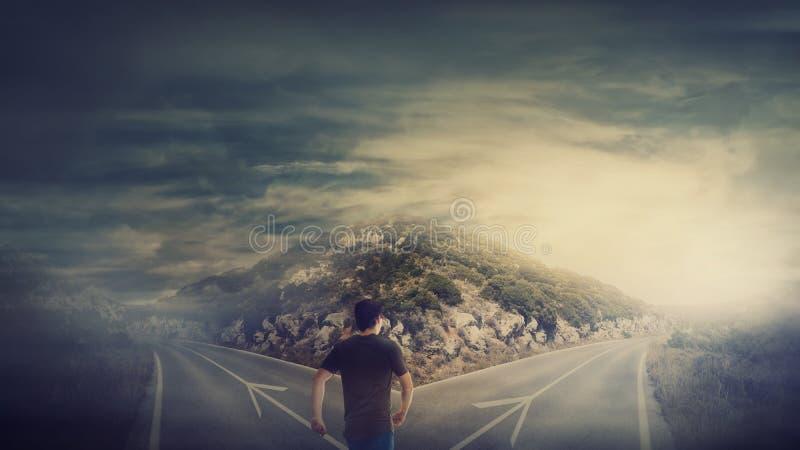 Το οπισθοσκόπο άτομο που περπατά μπροστά από το σταυροδρόμι ως δρόμος είναι χωρισμένο σε δύο διαφορετικούς τρόπους Επιλογή της σω στοκ εικόνες