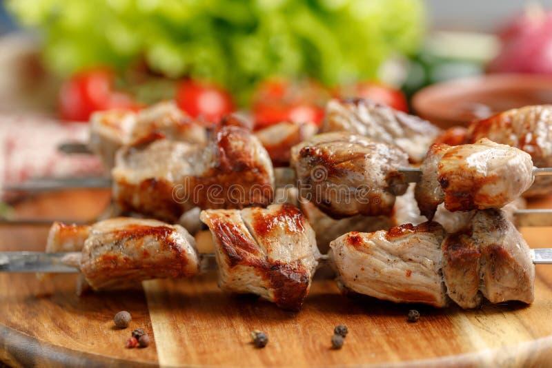 Το ορεκτικό shish kebab από το χοιρινό κρέας που μαγειρεύεται ανοίγει πυρ Ακόμα-ζωή σε ένα ξύλινο υπόβαθρο στοκ φωτογραφία