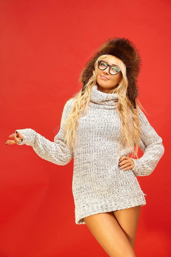 Το οριζόντιο πορτρέτο του όμορφου εύθυμου καυκάσιου θηλυκού στο καπέλο πουλόβερ και χειμώνα turtleneck, δείχνει στο κενό αντίγραφ στοκ εικόνα με δικαίωμα ελεύθερης χρήσης