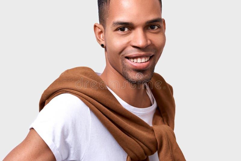 Το οριζόντιο στενό επάνω πορτρέτο του όμορφου σκοτεινός-ξεφλουδισμένου ατόμου που χαμογελά φορά την περιστασιακή μοντέρνη εξάρτησ στοκ εικόνες με δικαίωμα ελεύθερης χρήσης