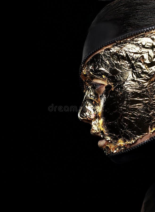 Το ορισμένο πρόσωπο της γυναίκας κάλυψε το χρυσό φύλλο αλουμινίου πέρα από το μαύρο υπόβαθρο. Μυστήριο στοκ εικόνες με δικαίωμα ελεύθερης χρήσης