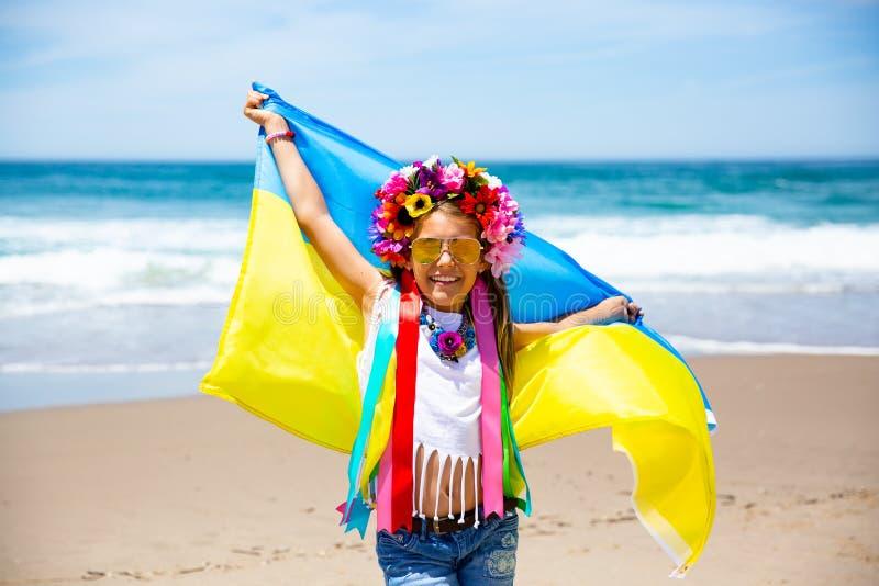 Το ουκρανικό κορίτσι φέρνει την μπλε και κίτρινη σημαία της Ουκρανίας που κυματίζει στο υπόβαθρο μπλε ουρανού στοκ εικόνα