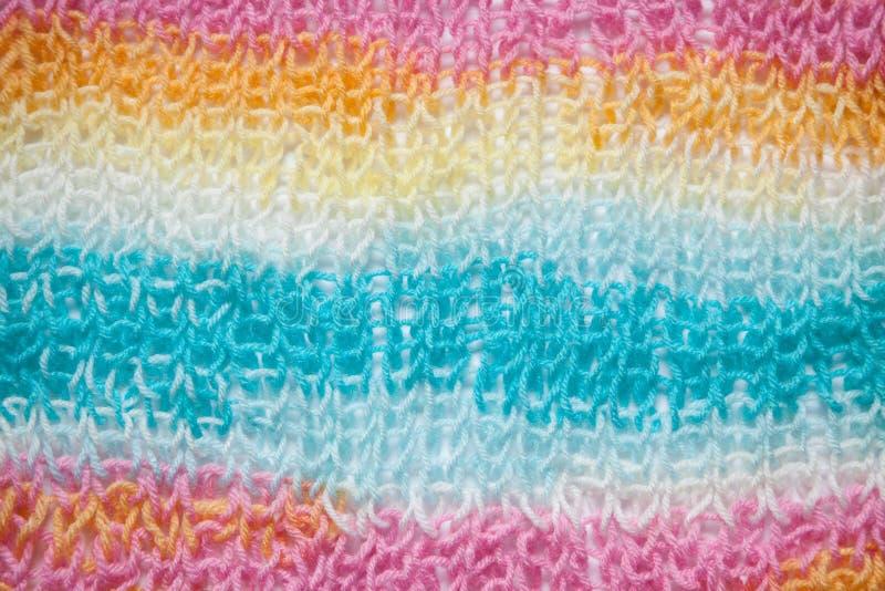 Το ουράνιο τόξο χρωματίζει το υπόβαθρο, που πλέκει τη σύσταση μαλλιού κοντά επάνω στοκ εικόνα