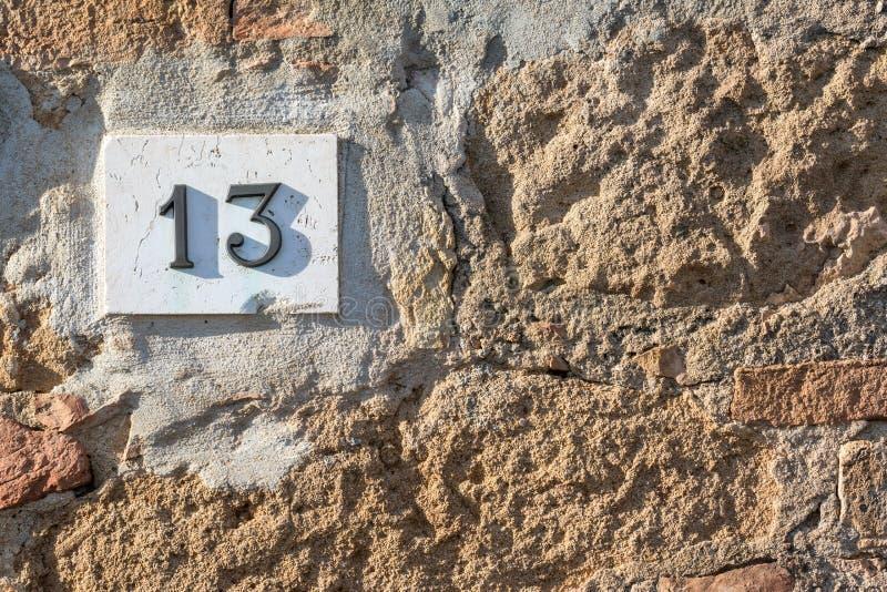 Το οδικό σημάδι σε ένα σπίτι που διαβάζει τον αριθμό δέκα τρία έκανε από τα μεταλλικά ψηφία σε μια μαρμάρινη βάση στοκ εικόνα