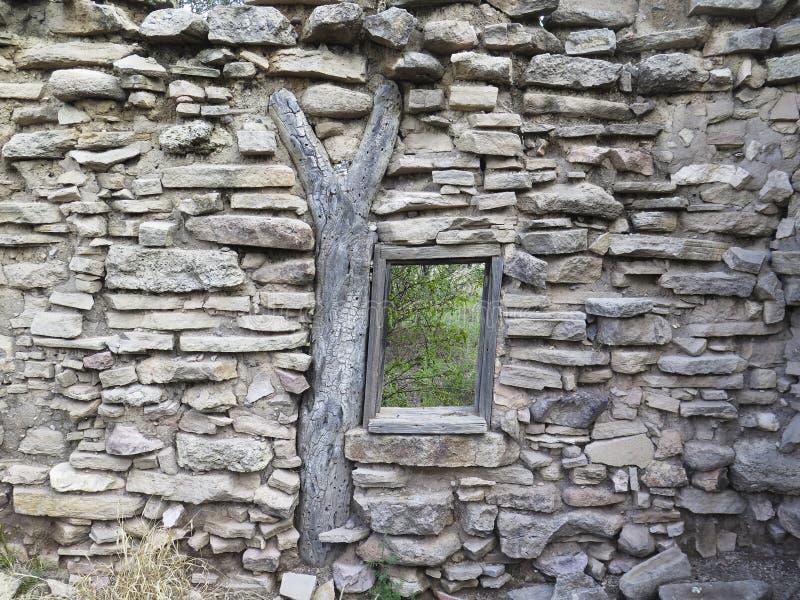 Το πέτρινο σπίτι καταστρέφει το παράθυρο με την υποστήριξη δέντρων στοκ εικόνες