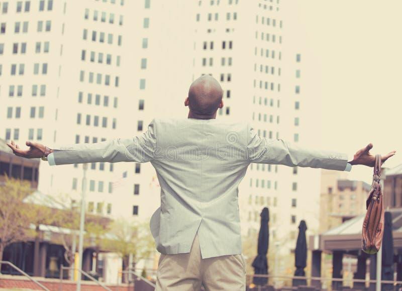 Το πίσω επιχειρησιακό άτομο άποψης γιορτάζει την επιτυχία ελευθερίας οπλίζει αυξημένο να ανατρέξει στον ουρανό στοκ εικόνες