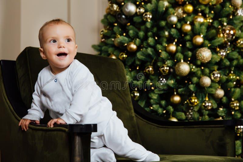 Το παιδάκι κάθεται σε μια πράσινη καρέκλα στους άσπρους ολισθαίνοντες ρυθμιστές ενάντια στο χριστουγεννιάτικο δέντρο στοκ εικόνες