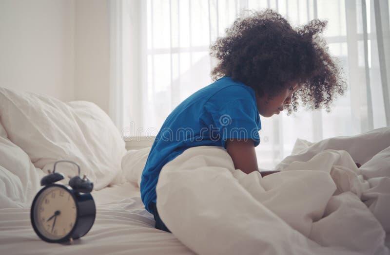 Το παιδάκι ξύπνησε ακριβώς από το ξυπνητήρι στοκ φωτογραφία