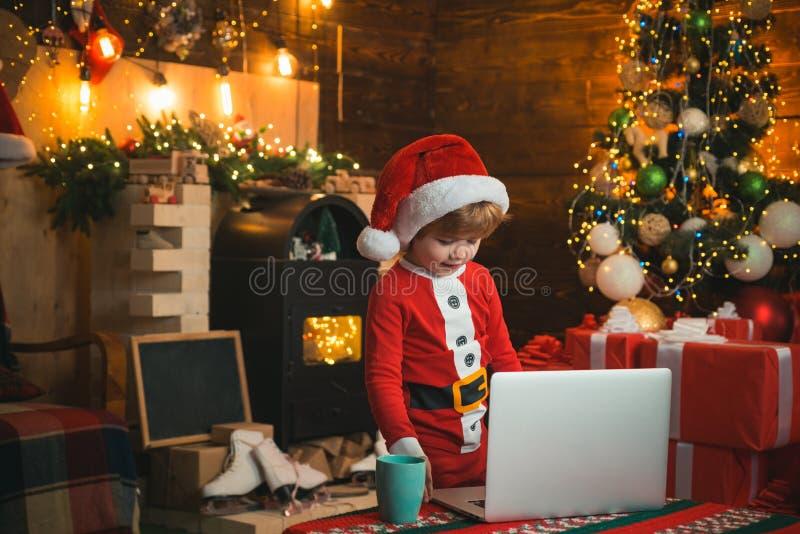 Το παιδάκι φορά τα ενδύματα Santa από το lap-top του Έννοια Χριστουγέννων Υπόβαθρο εστιών Φως Χριστουγέννων στοκ φωτογραφίες