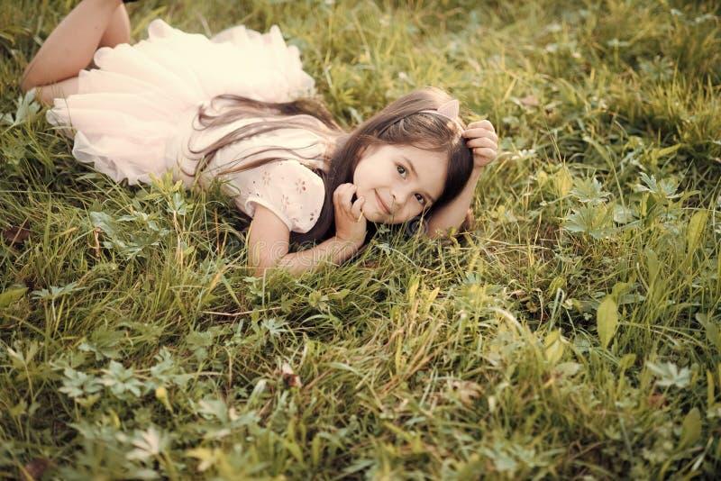 Το παιδάκι χαλαρώνει στην πράσινη χλόη, υγεία στοκ εικόνες