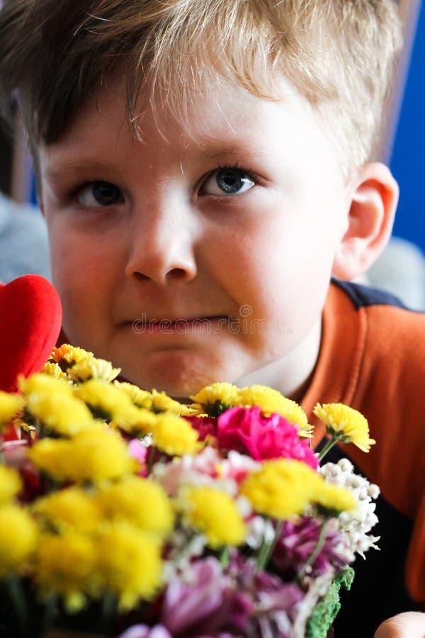 Το παιδί αγοράκι ρουθουνίζει την ανθοδέσμη λουλουδιών στοκ φωτογραφία με δικαίωμα ελεύθερης χρήσης