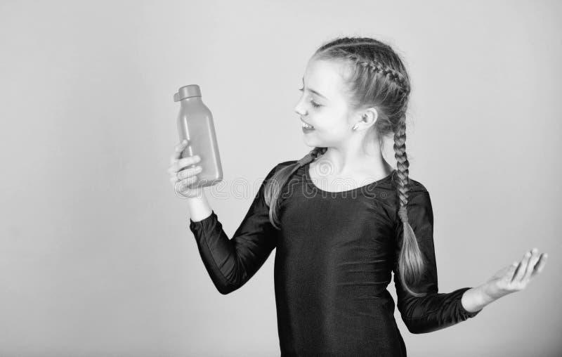 Το παιδί αισθάνεται τη δίψα μετά από την αθλητική κατάρτιση Gymnast κοριτσιών παιδιών χαριτωμένο μπουκάλι αθλητικής leotard λαβής στοκ φωτογραφία με δικαίωμα ελεύθερης χρήσης